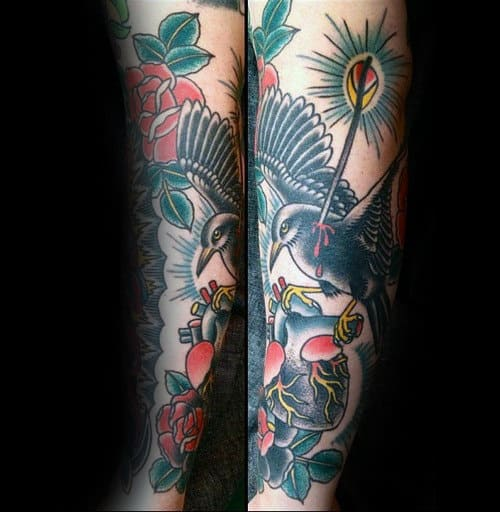 Guy With Forearm Tattoo Of Black Crow Flying With Heart Traditional Design
