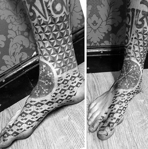Guy With Gray Snowflake And Tile Design Tattoo On Foot