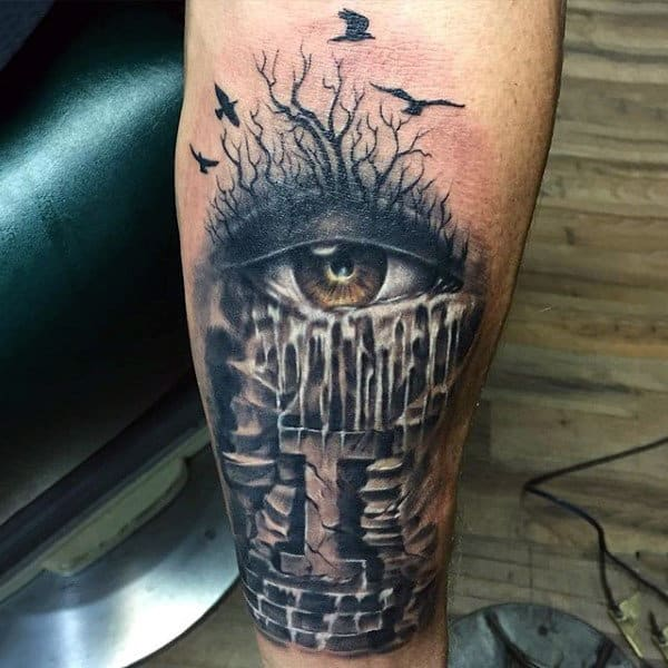 Guy With Haunted Brick Building And Eye Tattoo On Forearm