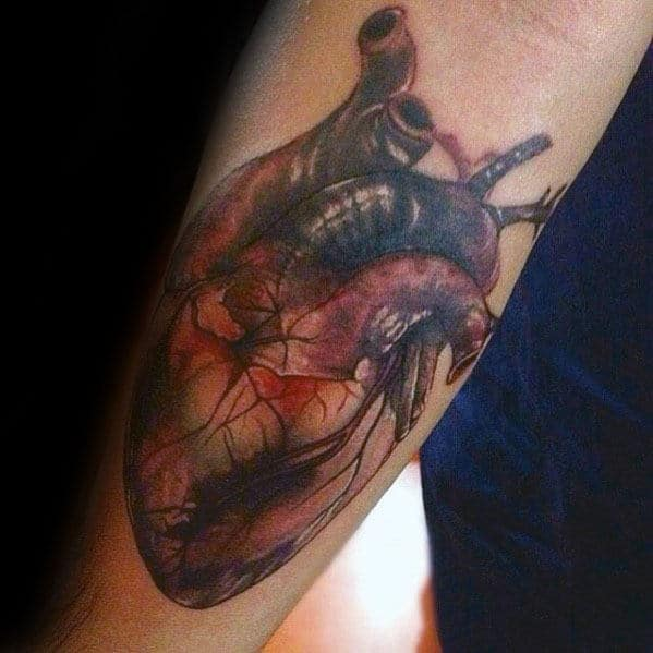 Guy With Realistic Heart Tattoo Design On Inner Forearm