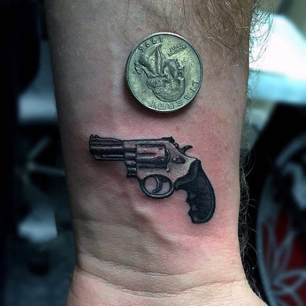 Guy With Small Pistol And 3D Coin Tattoo On Wrist