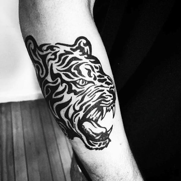 Guy With Tribal Outer Forearm Tiger Tattoo Design