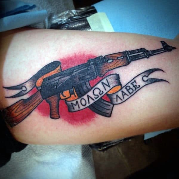 Guys Arms Ak 47 And Ribbon Tattoo