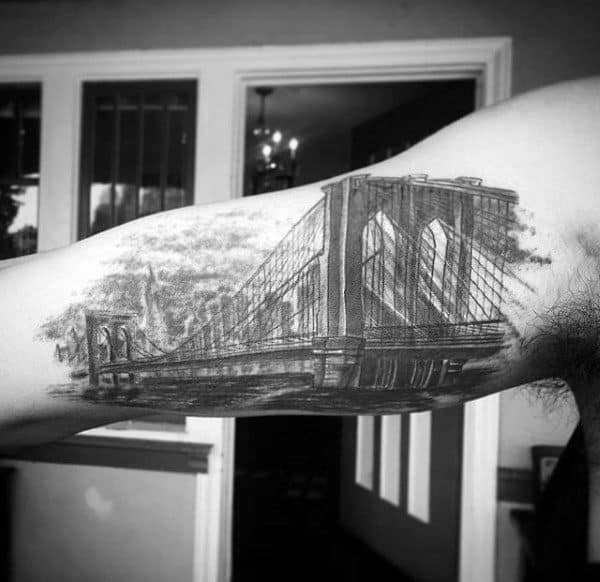 Guys Bicep Bridge Skyline With City Buildings Tattoo