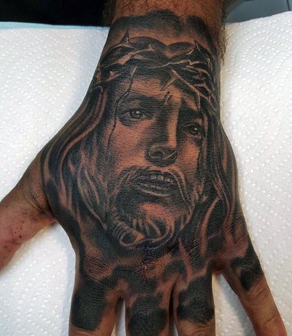 Guys Heavily Shaded Tattoo Of Jesus Christ On Hand