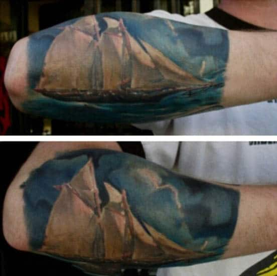 Guys Sailboat Painting Tattoo With Blue And White Ink On Arm