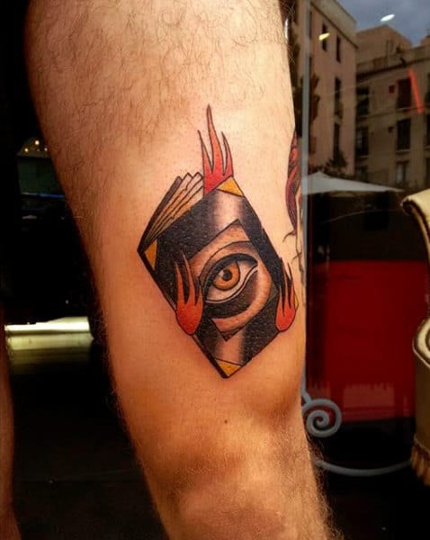 Guys Thighs Red Flaming One Eyed Book Tattoo
