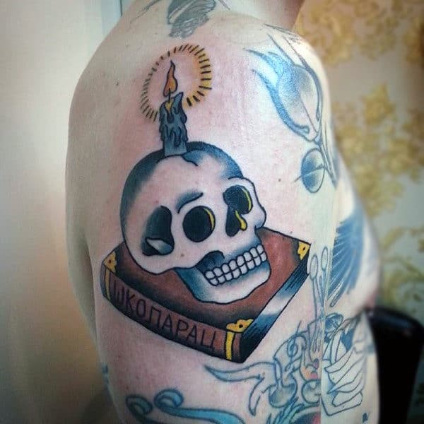 Guys Upper Arms Flaming Yellow Candle On Skull And Book Tattoo