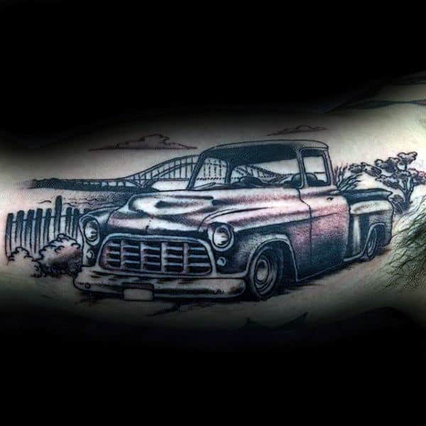 Guys Vintage Black And Grey Truck Tattoo With Landscape Of Bridge In Background On Arm