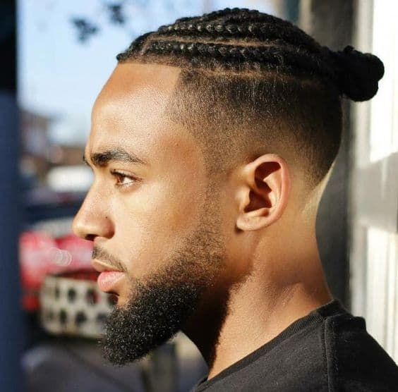 A black man wearing twists secured together on top to form a man bun