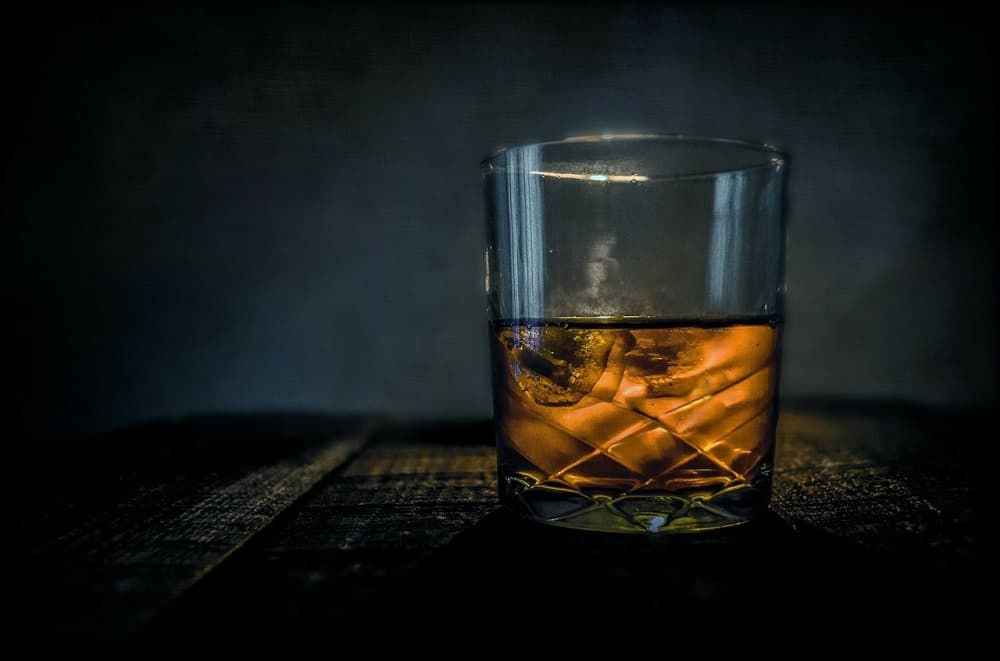half glass bourbon whisky with ice