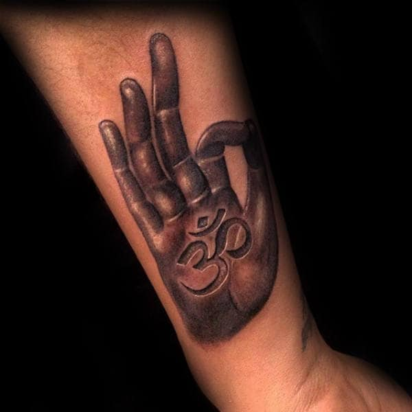Hand With Okay Sign And Om Tattoo On Mans Forearm