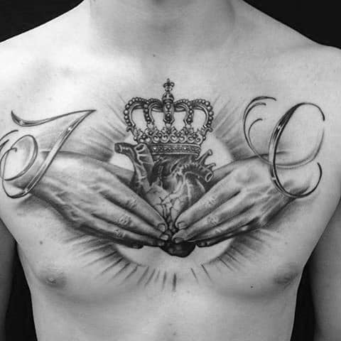 Hands Holding Crowned Heart Tattoo On Chest For Guys