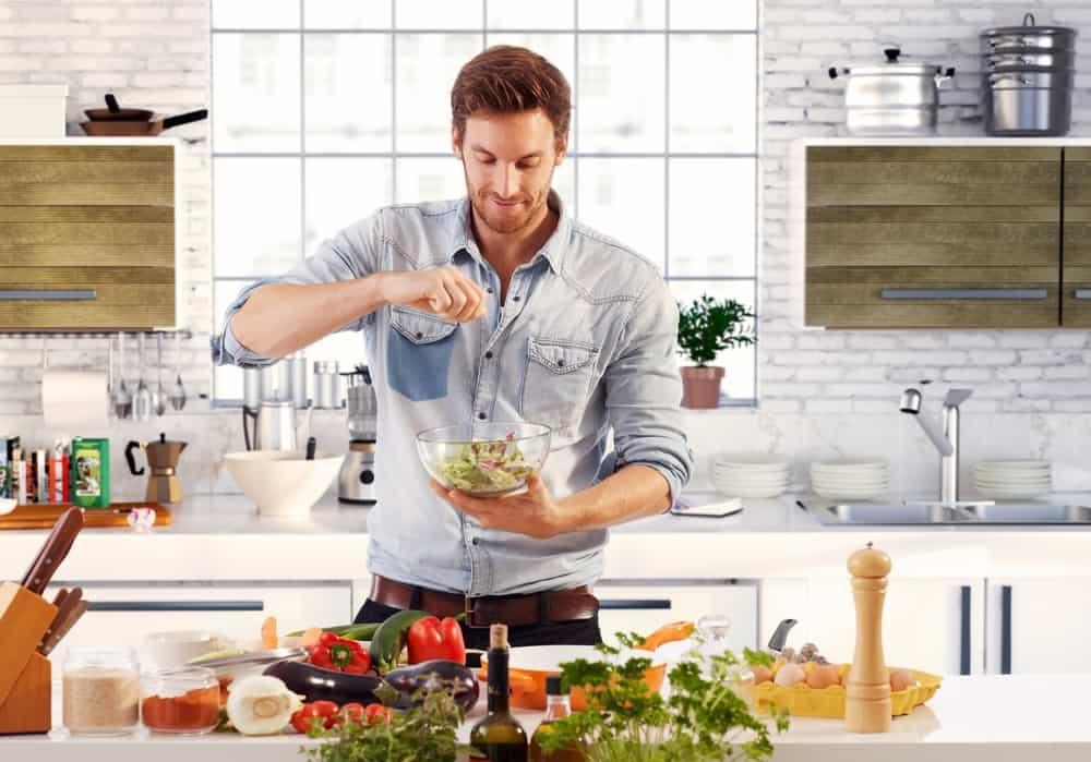 handsome man preparing salad in home