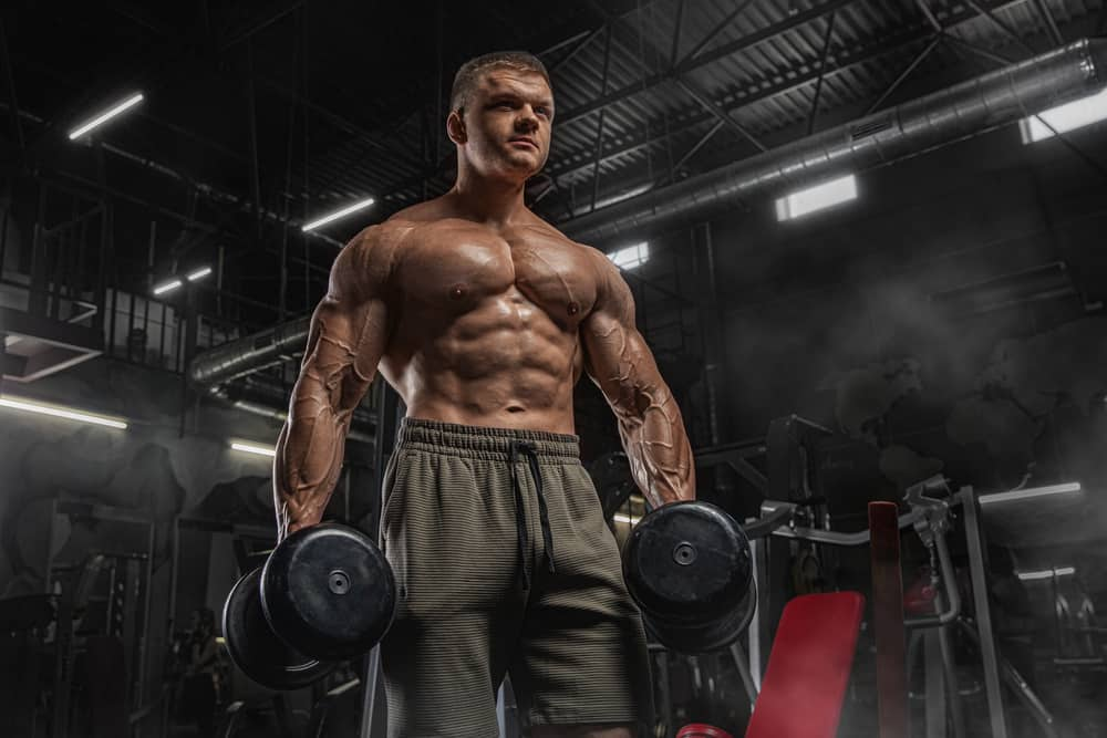 handsome sporty man with naked muscular torso doing weight lifting