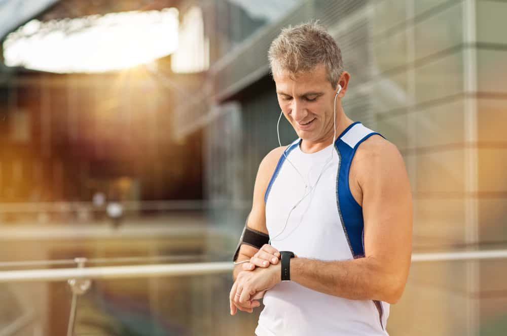 man looking heart rate monitor on his wrist watch