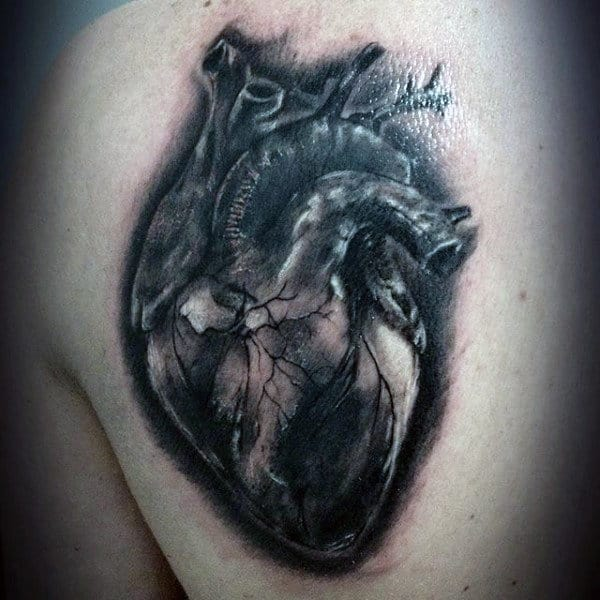 Heart Tattoo On Mans Back In Black Ink