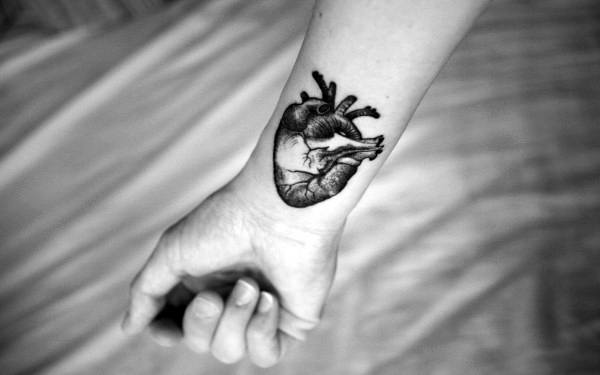Heart Tattoo On Mans Forearm In Blackwork Ink