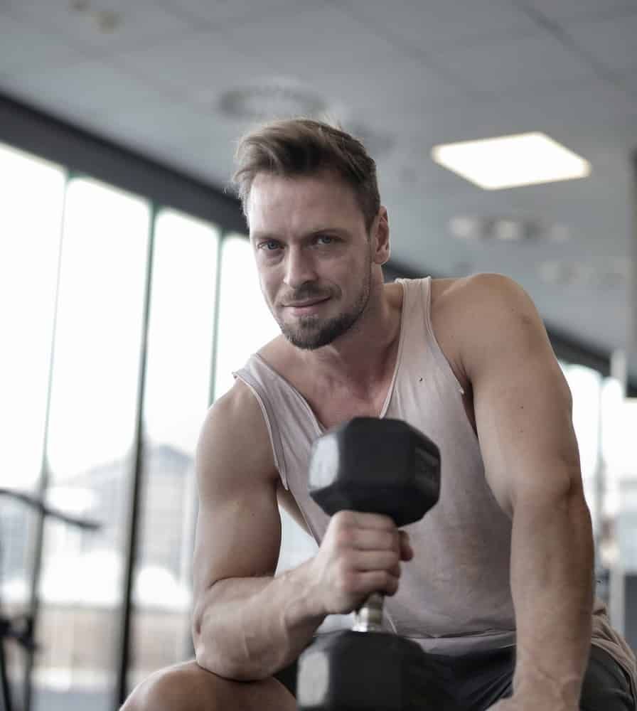 smiling man in tank top holding black dumbbell in gym