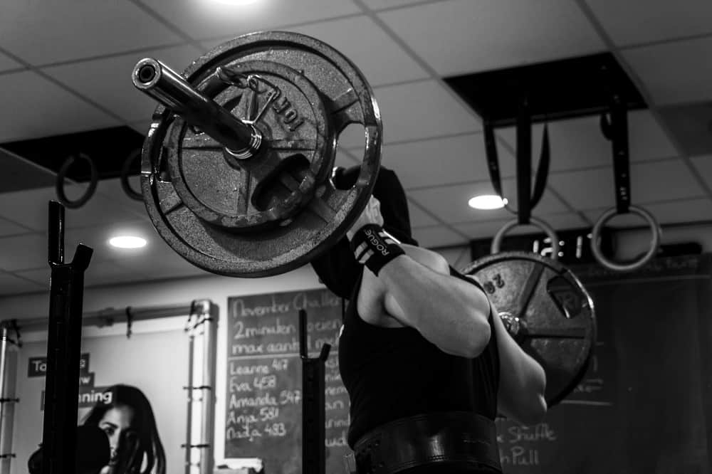 man stands in a gym holding a weighted barbell bar behind his back