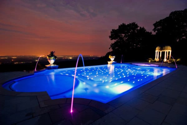 Home Swimming Pool At Night With Water Fountains And Neon Lighting