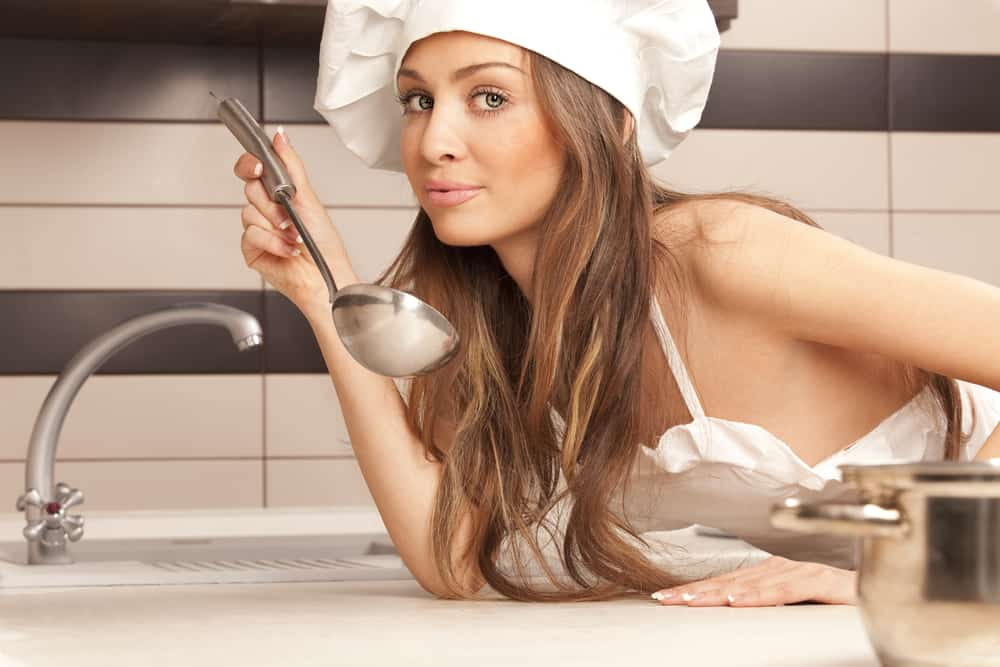 housewife tasting dish in kitchen
