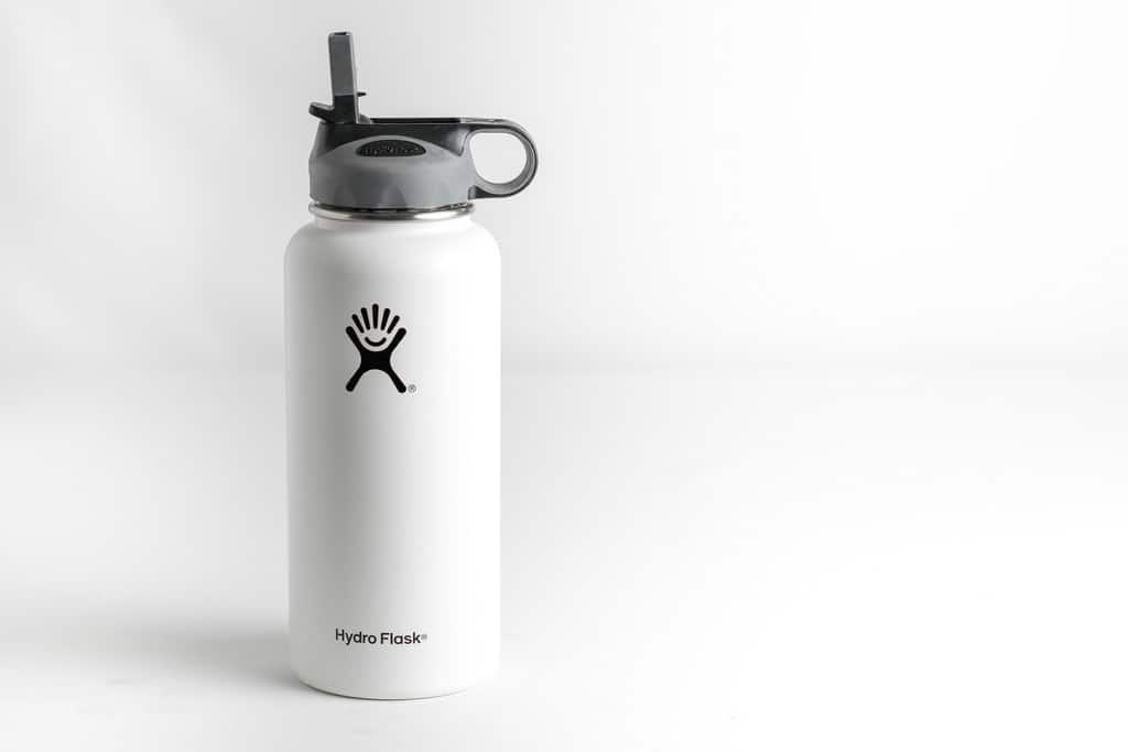 white hydroflask with company logo facing camera with white floor and white background