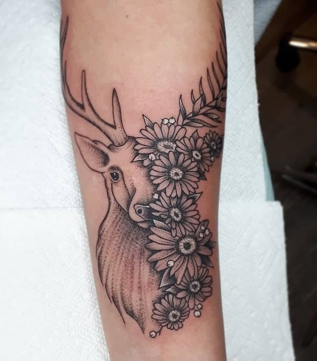 Forearm tattoo black and grey and white illustrative deer with daisies covering half its face