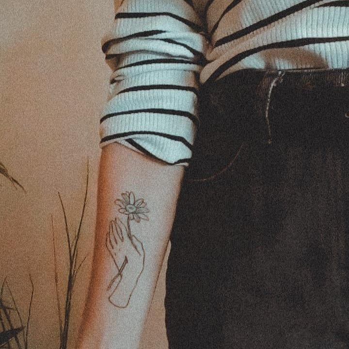 Forearm tattoo illustrative black and grey fine line daisy and hand