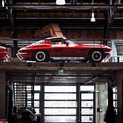 Industrial Dream Garage Design With Brilliant Red Classic Corvette