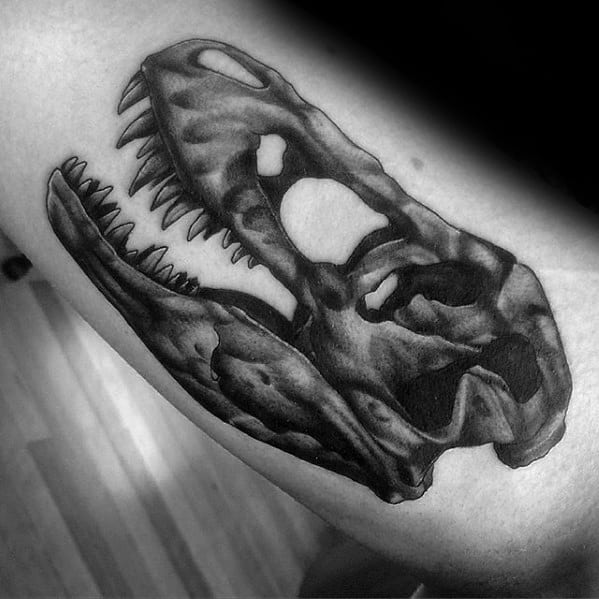 Inner Arm Bicep Dinosaur Skull Jurassic Park Tattoo Design On Man