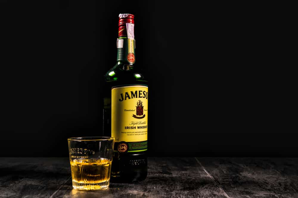 jameson whiskey bottle with glass and ice cubes