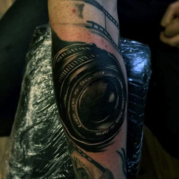 Jet Black Camera Lens Tattoo Male Forearms