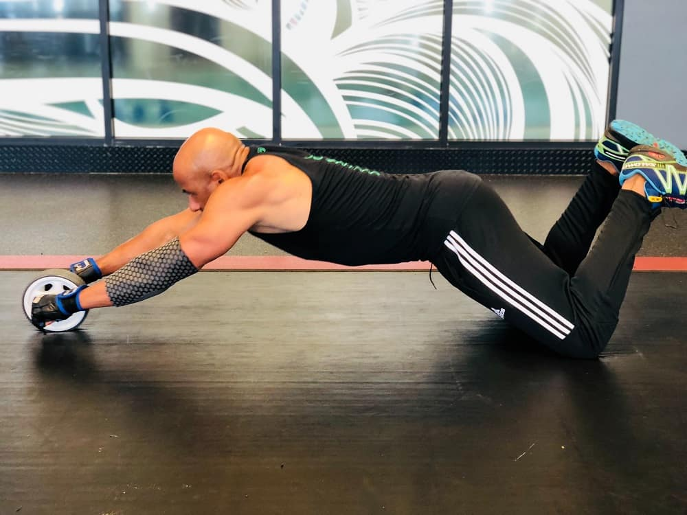 man in a gym performs a kneeling ab wheel workout, fully extended