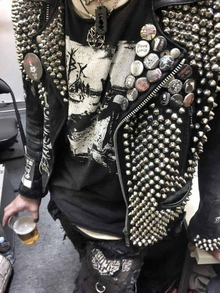 Man wearing a leather jacket with pins and spikes