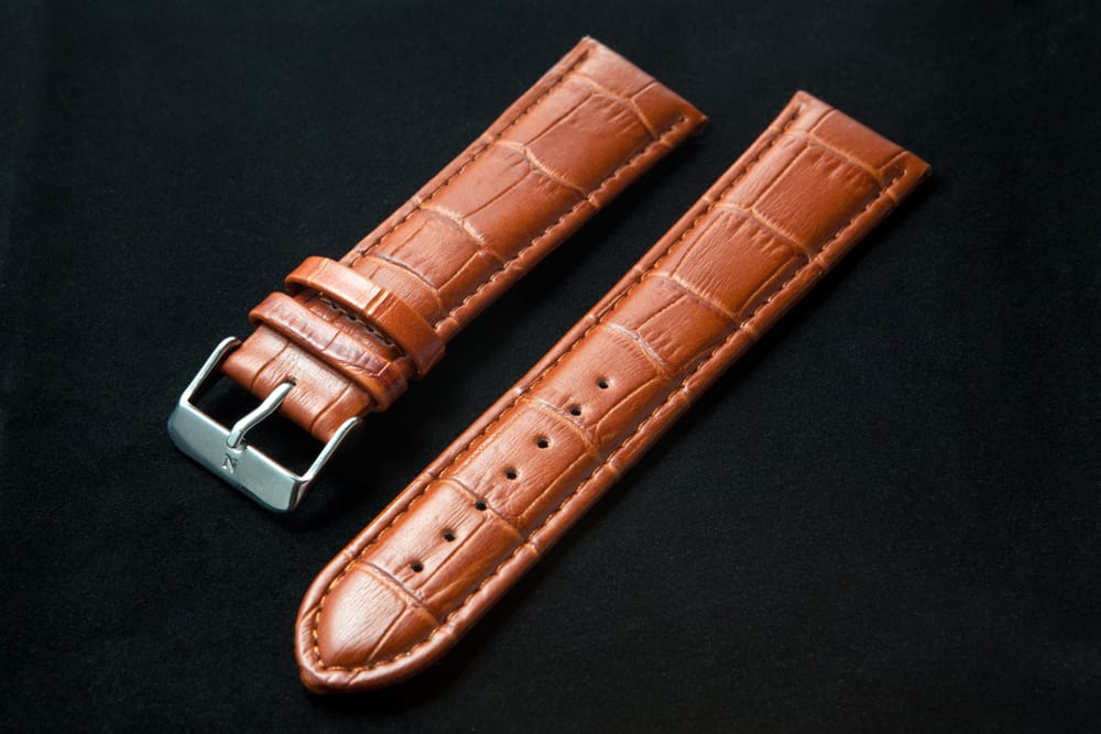 leather watch wrist strap laying on black background