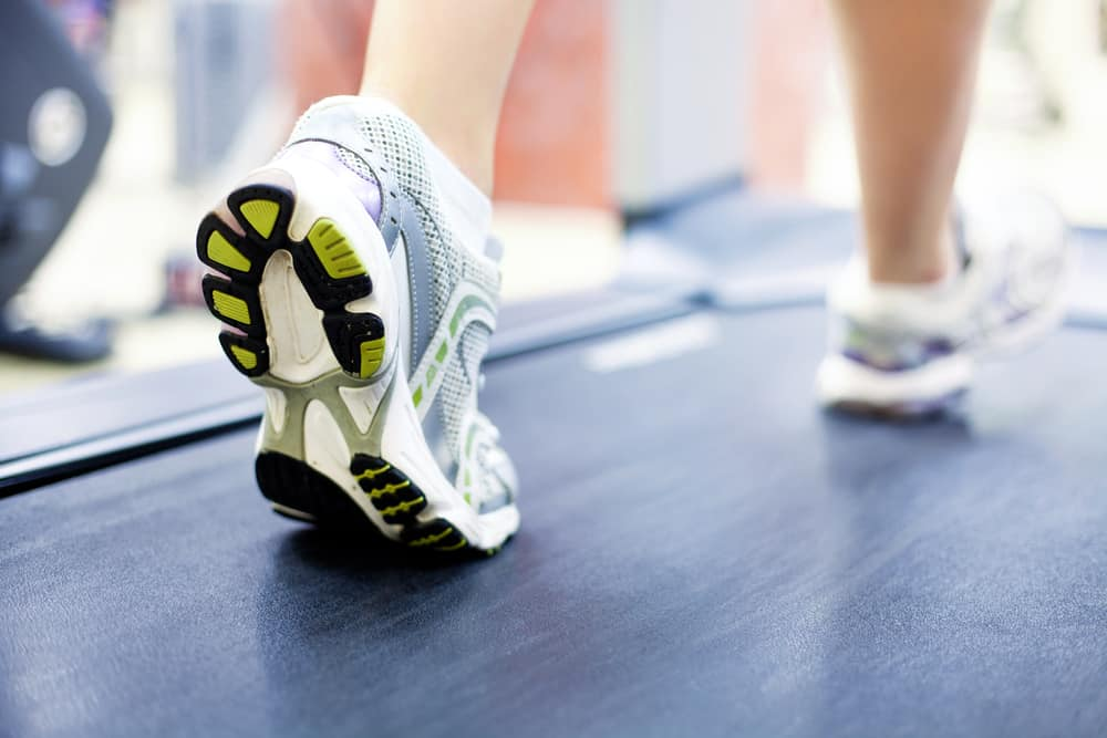 women legs on treadmill with white shoes