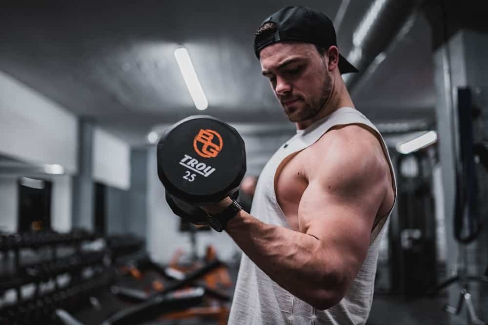 man in a gym lights a dumbbell upwards