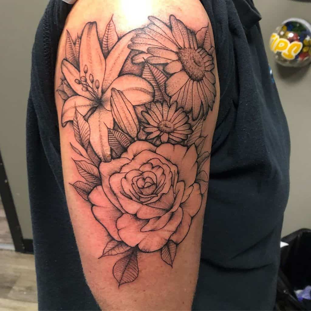 Upper arm and shoulder tattoo black and grey line work lily rose daisy bouquet