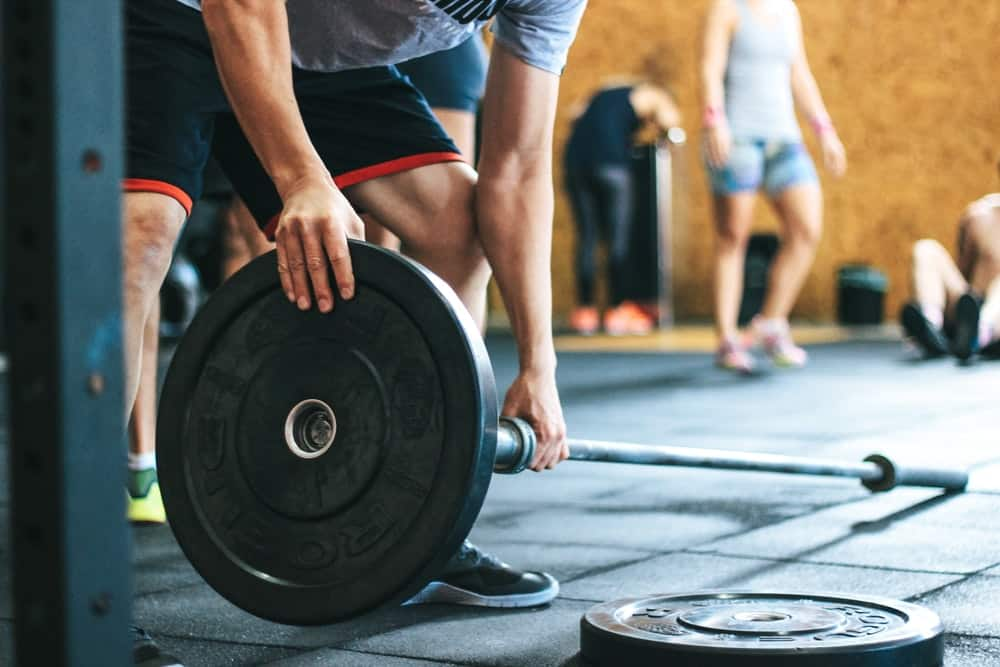 an athlete loads up a barbell with weight in a gym