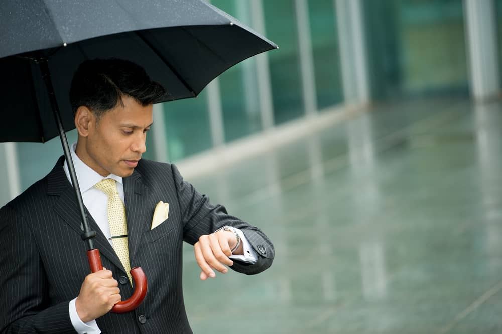 man in rain with umbrella looking time on his watch