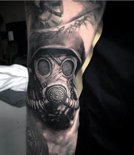 Lower Arm Gas Mask Male Tattoo With Clock In Black Ink