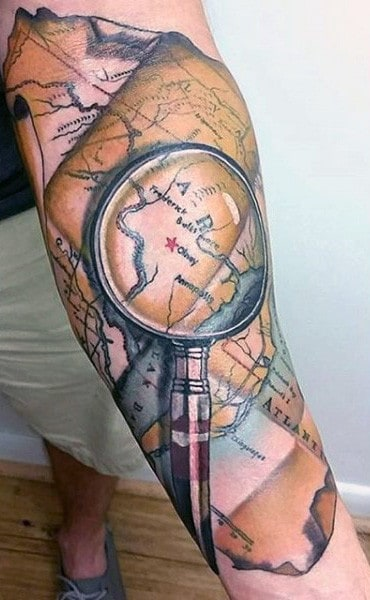 50 world map tattoo designs for men adventure the globe magnifying glass world map male tattoo on forearm gumiabroncs Gallery