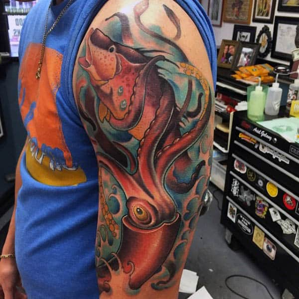 Male Arm Tattoo Of Squid With Tentacles Wrapped Around Fish
