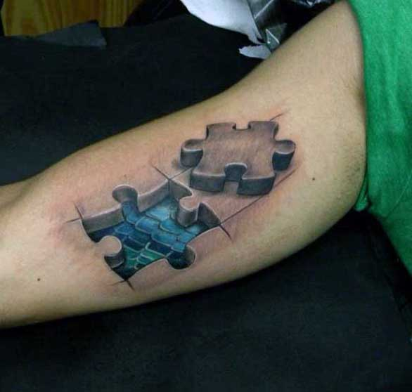 Male Tattoo Puzzle On Bicep With Blue Scales Inside