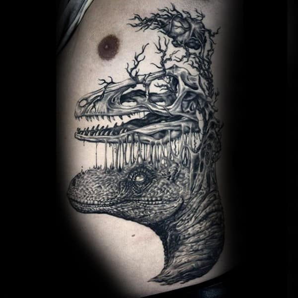 Male With Bony Branches Sprouting Out Of Dinosaur Tattoo On Side Ribs