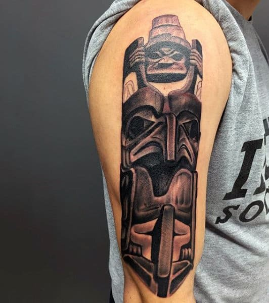 Male With Carved Dark Shaded Totem Pole On Upper Arm Tattoo