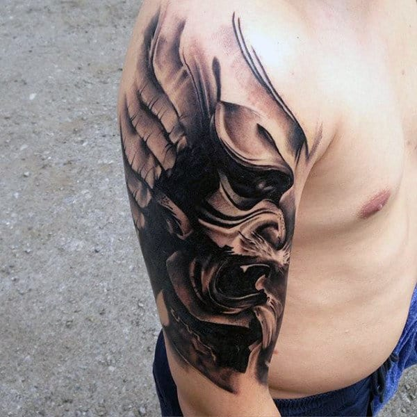 Male With Creative Tattoo Of Shaded Mask With Wings On Arm