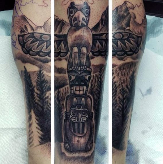Male With Eagle And Demon Totem Pole And Mountainscape Calf Tattoo
