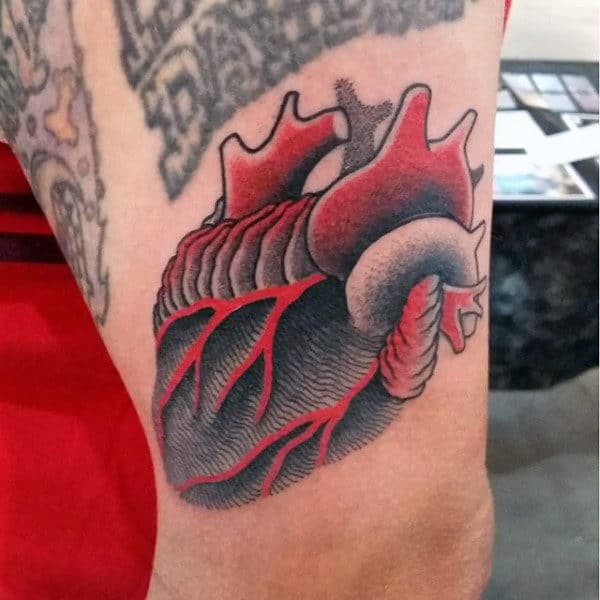 Male With Heart Tattoo In Red And Black On Thigh